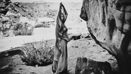 Girl in long dress in Egupt desert.