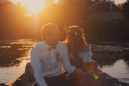 Couple in a boat on a river. Sunset.